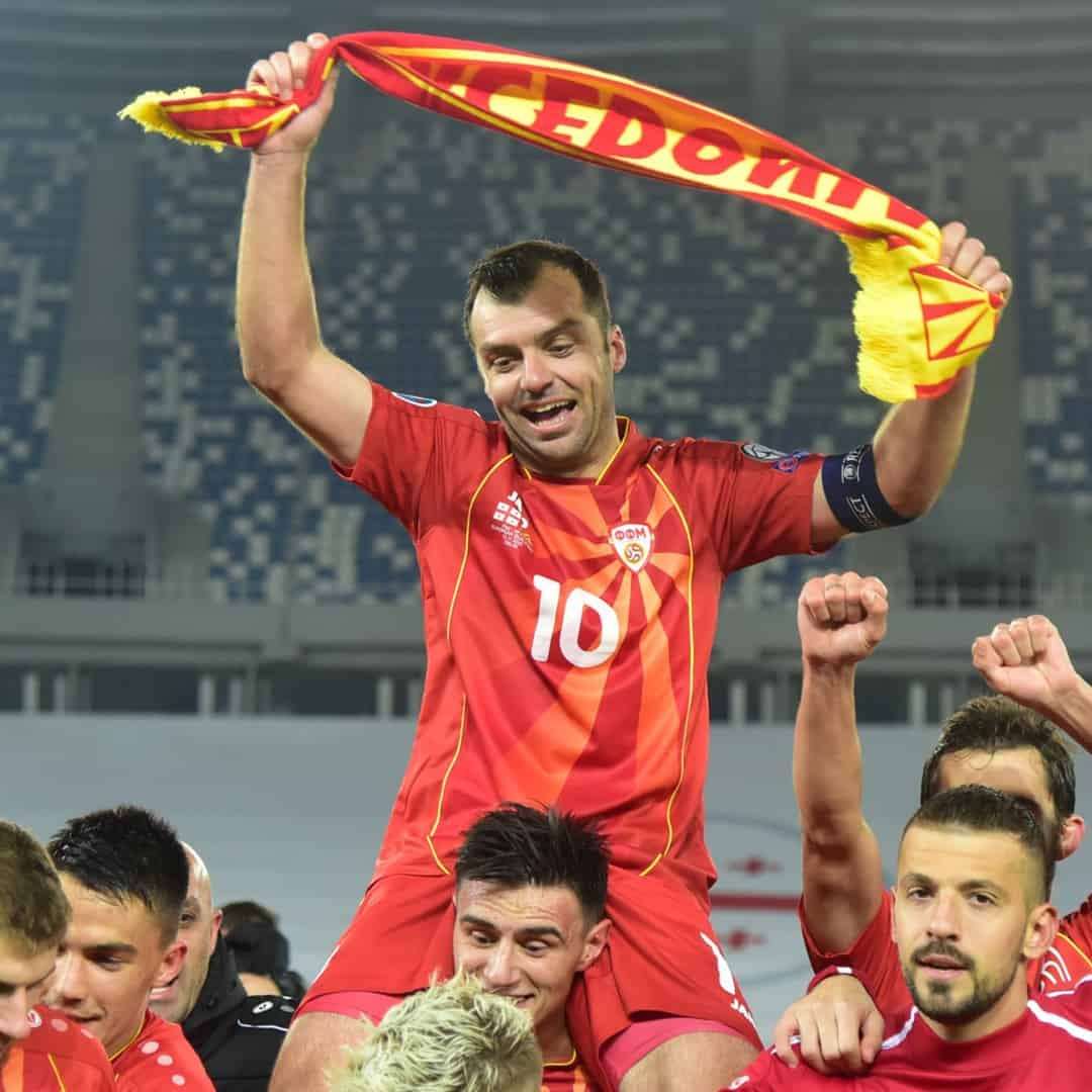 Goran Pandev waving a scarf with the words Macedonia on it as well as the Macedonian flag showcased as Elif Elmas carries him on his shoulders.