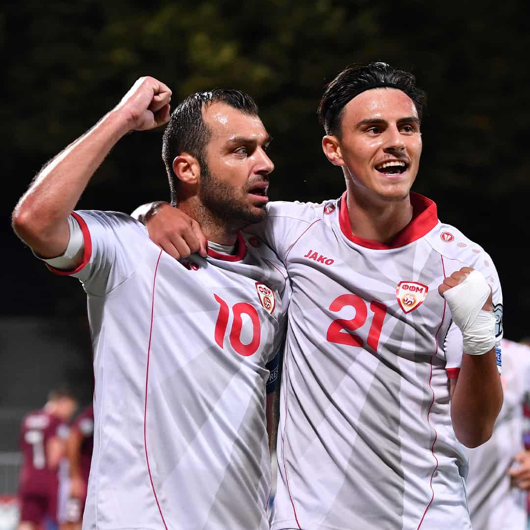 Goran Pandev in a white jersey, next to Elif Elmas cheering along with his hand up in the air in a fist.