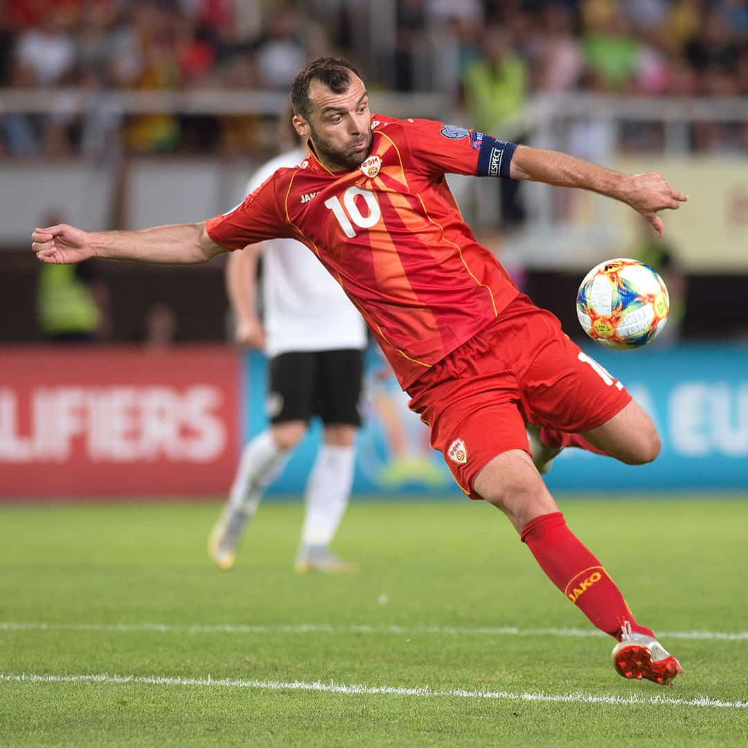 Goran Pandev ina red jersey, red shorts and red socks getting ready to sky-rocket kick the ball towards its goal.