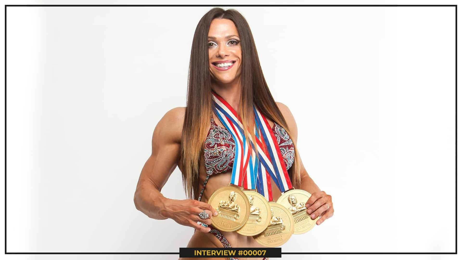 Oksana Grishina sstanding in front of the carema holding her four golden medals