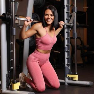 Ivana Kocevska smiling after a completed exercise at the gym, she is on her knees at the ground and wears pink clothing.