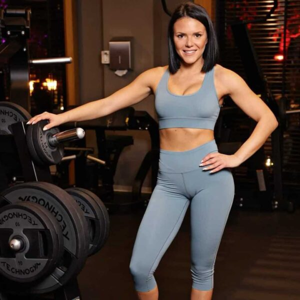 Ivana Kocevska posing next to a bunch of weights at the gym and smiling at the camera.