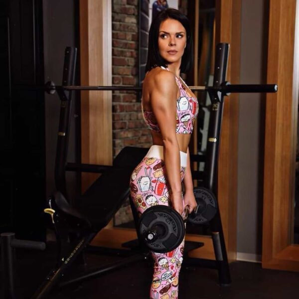 Ivana Kocevska training her shoulders at the gym while wearing pink clothing.