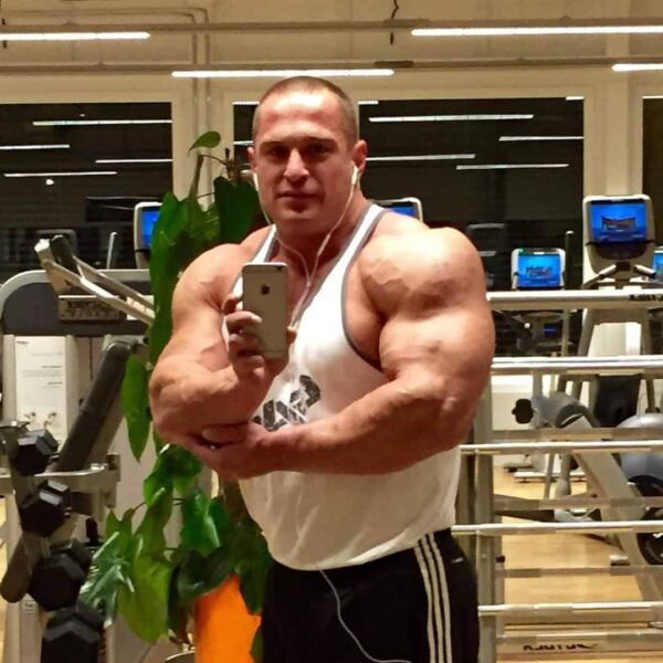 Ljubivoj Bakic at the gym taking a selfie of himself flexing his muscles while wearing a white shirt.