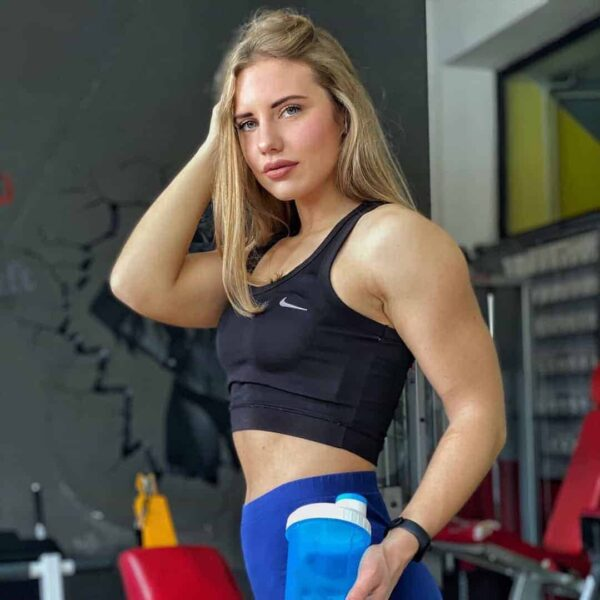 Sara Stojanoska at the gym posing for the camera and holding a blue bottle.
