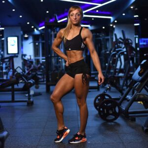 Gabriela Zafirova standing at a gym flexing her body's muscles