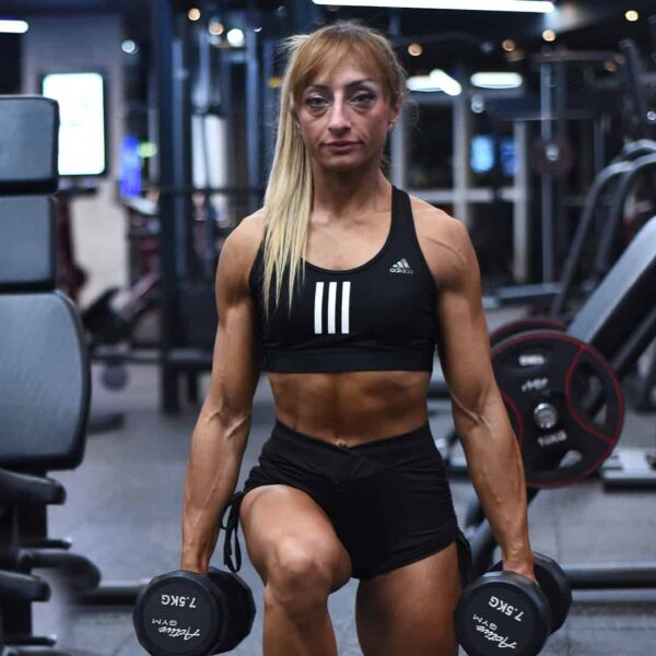 Gabriela Zafirova training at the gym while holding two weights in her hands training her legs