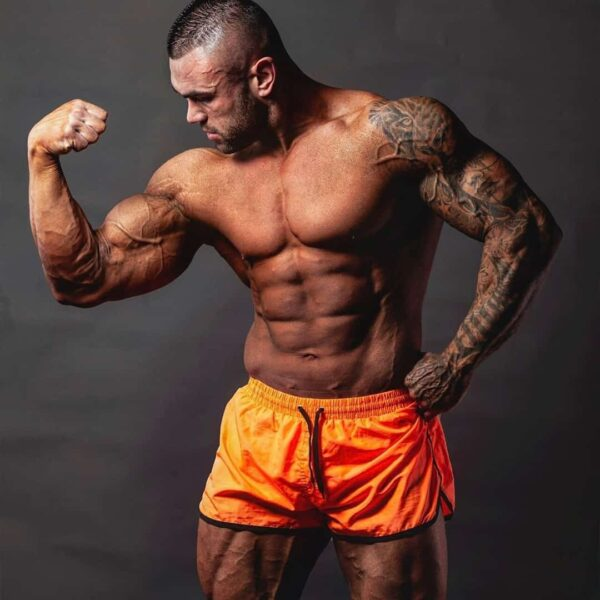 Hristijan Manasievski flexing his biceps muscles while wearing orange clothes, he has tatoos on his left hand entirely