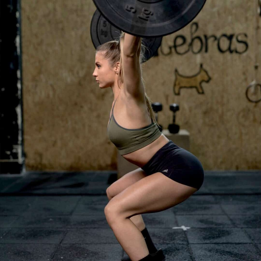 An image of Silvana Veljanoska holding weights over her shoulders in a squatting position