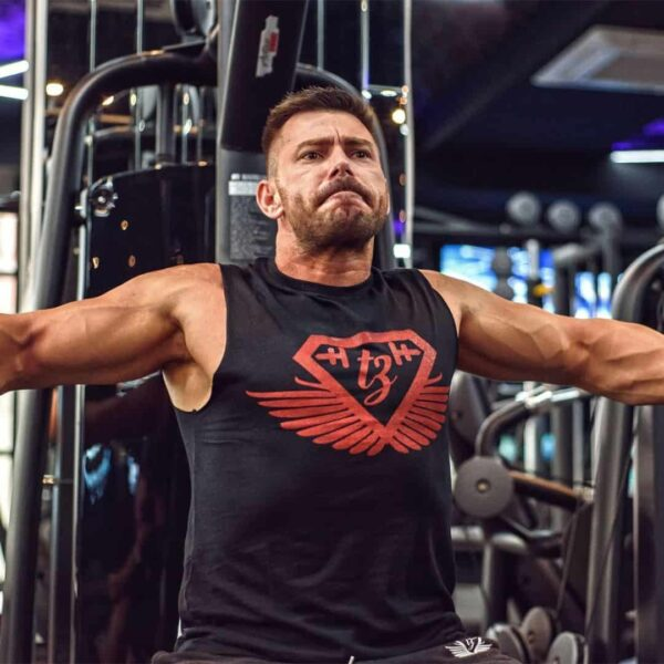 Trajche Stojanov training his chest in a gym on a machine specifically designed for that function