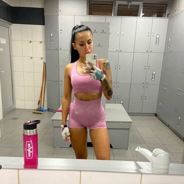 Viktorija Zajkova taking an image of herself in the mirror at a locker room at the gym where she is wearing pink training clothes