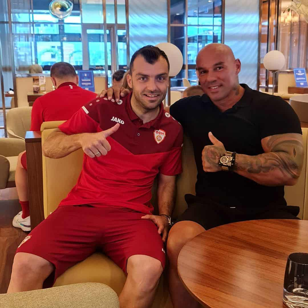 An image of Goran Pandev and Tose Zafirov. Both of them are looking towards the camera, smiling, and showing a 'like' with their hands. Goran Pandev is wearing a red football dress from FFM, while Tose is dressed in a black t-shirt.