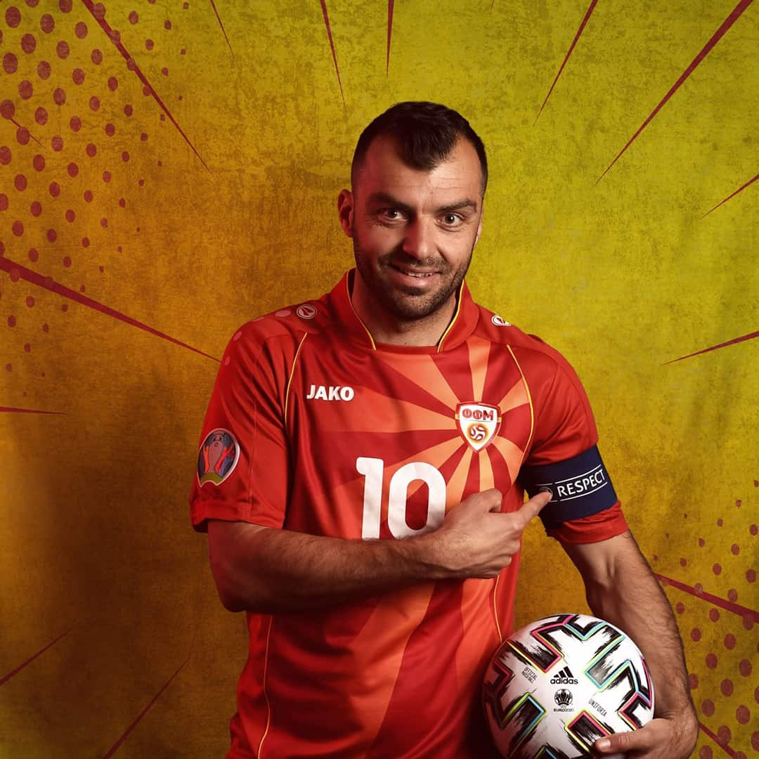 An image of Goran Pandev, a famous Macedonian footballer. He is wearing the national team jersey for The UEFA European Football Championship. He is holding a football in his hand, smiling at the camera in front of a yellow background.